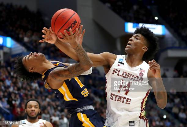 Ja Morant of the Murray State Racers and Terance Mann of the Florida State Seminoles battle for the ball in the second half during the second round...