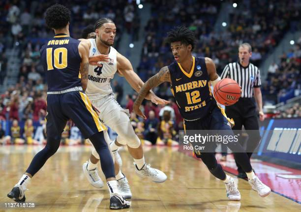 Ja Morant of the Murray State Racers drives past Theo John of the Marquette Golden Eagles during their first round game of the 2019 NCAA Men's...