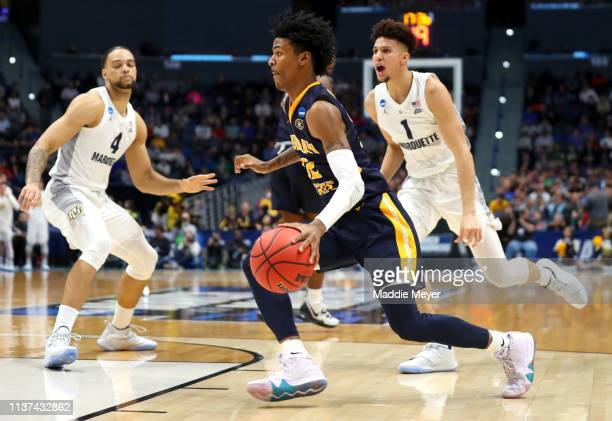 Ja Morant of the Murray State Racers drives the ball against Theo John and Brendan Bailey of the Marquette Golden Eagles during the first round game...