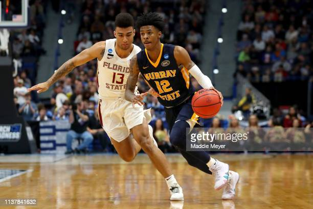 Ja Morant of the Murray State Racers is defended by Anthony Polite of the Florida State Seminoles in the second half during the second round of the...