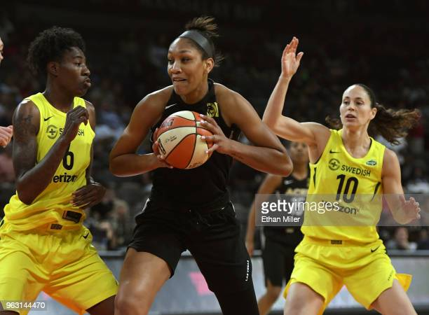 A'ja Wilson of the Las Vegas Aces drives against Natasha Howard and Sue Bird of the Seattle Storm during the Aces' inaugural regularseason home...
