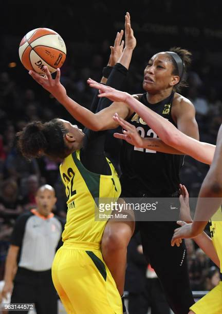 A'ja Wilson of the Las Vegas Aces drives to the basket against Alysha Clark of the Seattle Storm during the Aces' inaugural regularseason home opener...