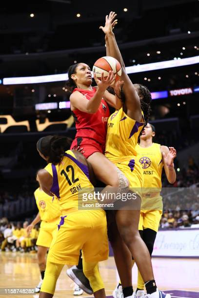 A'ja Wilson of the Las Vegas Aces goes to the basket against Chelsea Gray and Kalani Brown of the Los Angeles Sparks during a WNBA basketball game at...
