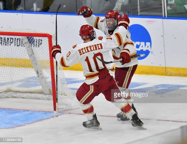 Jaakko Heikkinen and Jarid Lukosevicius of the Denver Pioneers celebrate after Lukosevicius scored an empty net goal against the American...