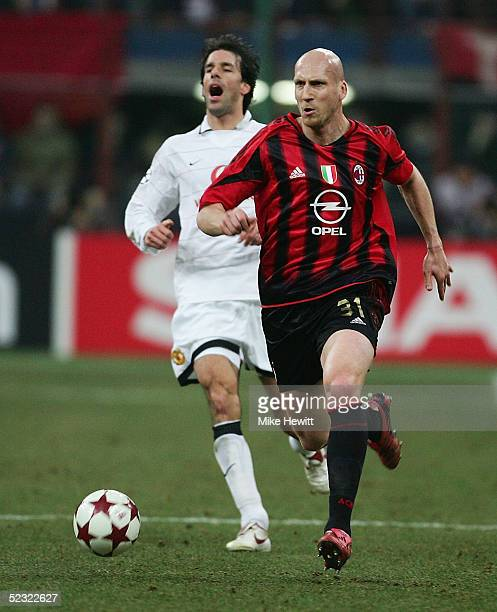 Jaap Stam of AC Milan charges through as Ruud van Nistelrooy of Manchester United warns his teammates during the UEFA Champions League match between...