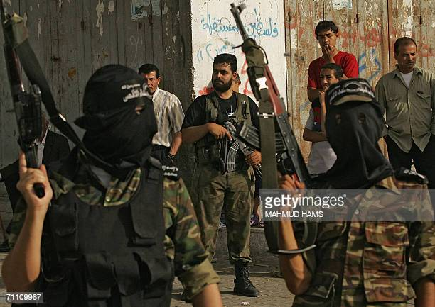 Hamas policeman stands guard as mlitants from Al-Aqsa Martyrs Brigades, the armed wing of the Fatah movement , parade in the streets of the northern...