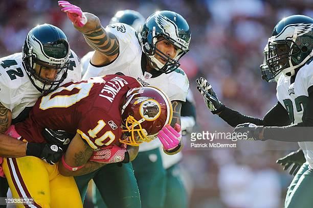 Jabar Gaffney of the Washington Redskins is tackled by Kurt Coleman and Jason Babin of the Philadelphia Eagles in the second hallf during a game at...