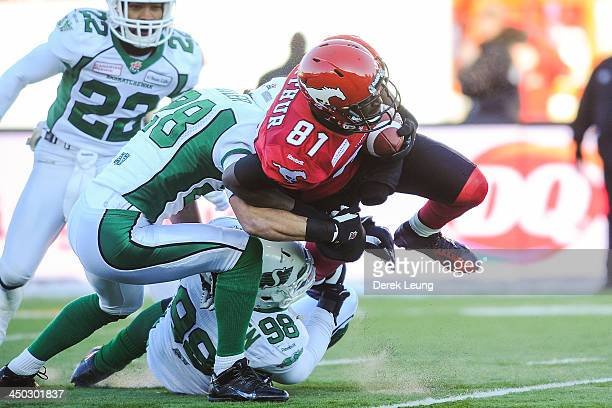 Jabari Arthur of the Calgary Stampeders carries the ball against Craig Butler and Kenny Rowe of the Saskatchewan Roughriders during a CFL game at...