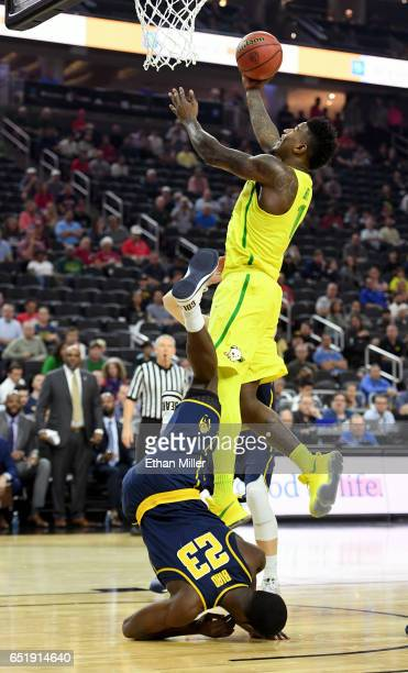 Jabari Bird of the California Golden Bears falls to the court as Jordan Bell of the Oregon Ducks drives to the basket during a semifinal game of the...
