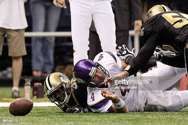 Jabari Greer and Scott Fujita of the New Orleans Saints scramble for a loose ball against Brett Favre of the Minnesota Vikings during the NFC...