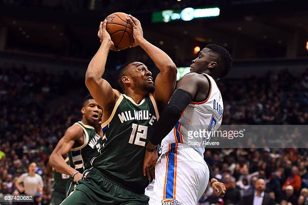 Jabari Parker of the Milwaukee Bucks drives to the basket against Victor Oladipo of the Oklahoma City Thunder during a game at the BMO Harris Bradley...