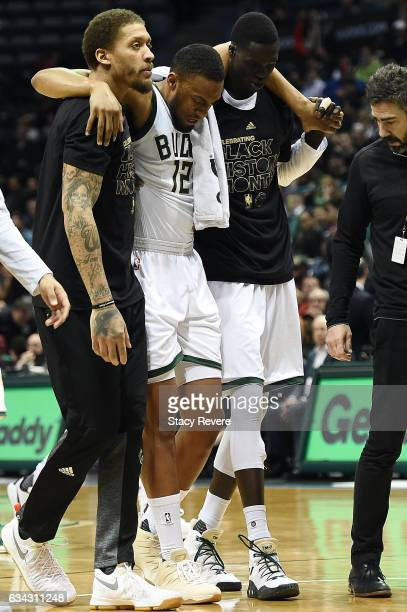 Jabari Parker of the Milwaukee Bucks is helped off the court by Michael Beasley and Thon Maker during the second half of a game against the Miami...
