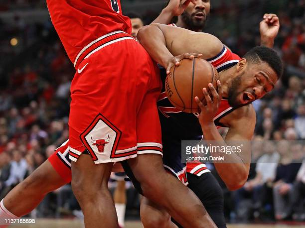 Jabari Parker of the Washington Wizards falls as he tries to moves against Cristiano Felicio of the Chicago Bulls at the United Center on March 20...
