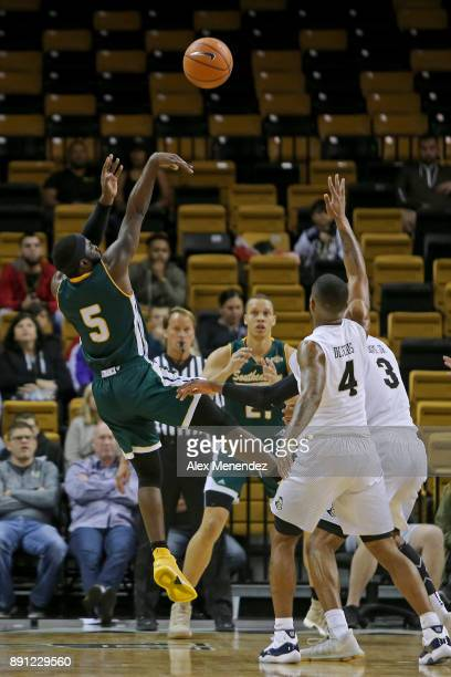 Jabbar Singleton of the Southeastern Louisiana Lions shoots the ball over Ceasar DeJesus and AJ Davis of the UCF Knights during a NCAA basketball...