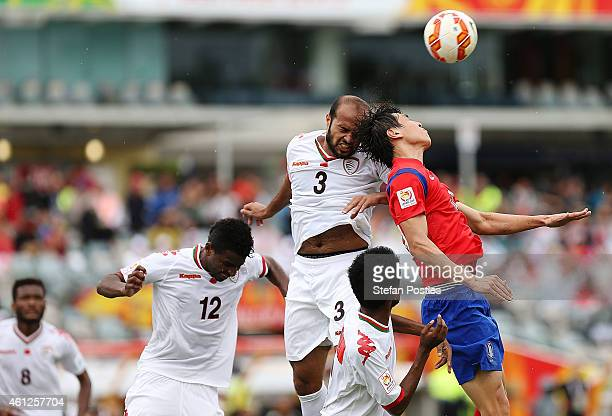 Jaber Al Owaisi of Oman and Koo Ja Cheol of Korea Republic contest a high ball during the 2015 Asian Cup match between Korea Republic and Oman at...