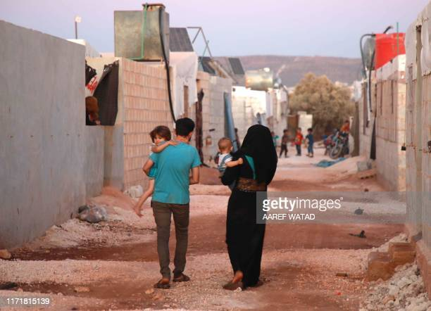 Jaber Karawan walks with his wife Walaa as they carry their two children at a camp for displaced Syrians in Atme in the northwestern Idlib province...