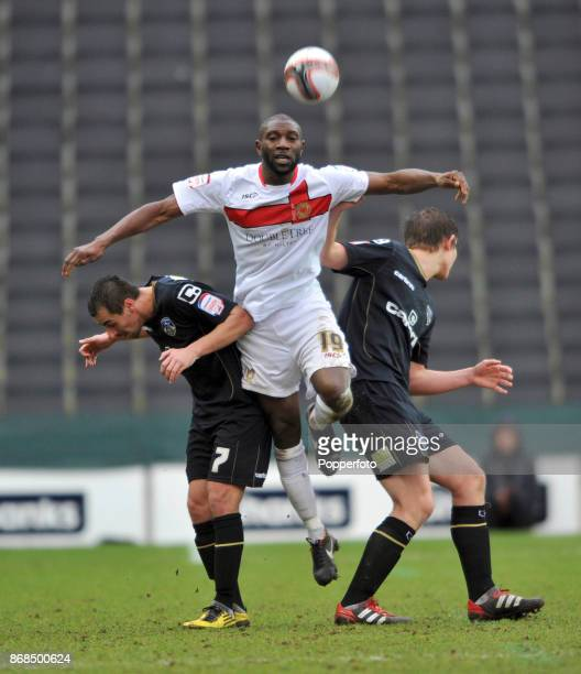 Jabo Ibehre of Milton Keynes Dons is challenged by Filipe Morais and James Tarkowski of Oldham Athletic in action during a Npower League One match at...