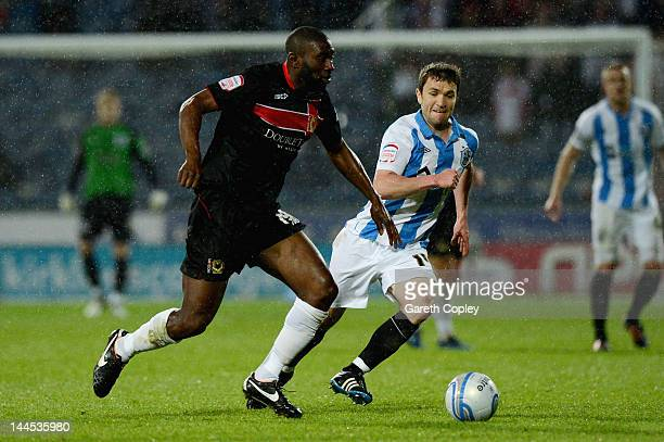 Jabo Ibehre of MK Dons gets past Damien Johnson of Huddersfield during the npower League One Semi Final 2nd Leg match between Huddersfield Town and...