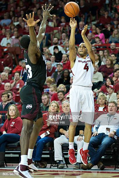 Jabril Durham of the Arkansas Razorbacks shoots a jump shot over Travis Daniels of the Mississippi State Bulldogs at Bud Walton Arena on January 9...