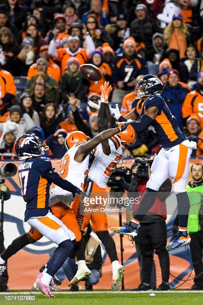 Jabrill Peppers of the Cleveland Browns intercepts a pass intended for Courtland Sutton of the Denver Broncos as T.J. Carrie and DaeSean Hamilton...