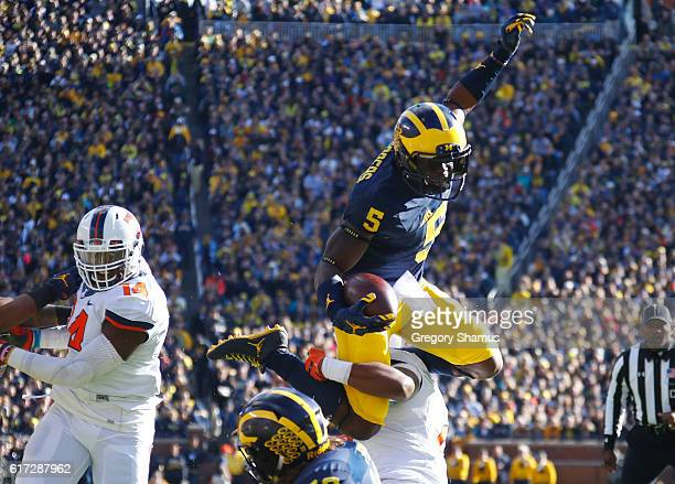Jabrill Peppers of the Michigan Wolverines jumps over Julian Jones of the Illinois Fighting Illini during a first quarter run on October 22 2016 at...