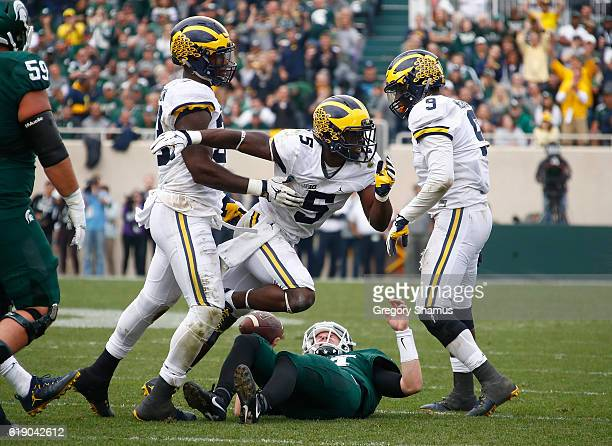 Jabrill Peppers of the Michigan Wolverines reacts to a fourth quarter sack of Brian Lewerke of the Michigan State Spartans at Spartan Stadium on...