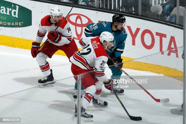 Jaccob Slavin and Brett Pesce of the Carolina Hurricanes and Tomas Hertl of the San Jose Sharks wait for the puck to pop out of the corner at SAP...