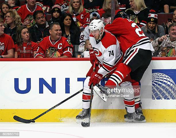 Jaccob Slavin of the Carolina Hurricanes battles for the puck along the boards with Ryan Garbutt of the Chicago Blackhawks at the United Center on...
