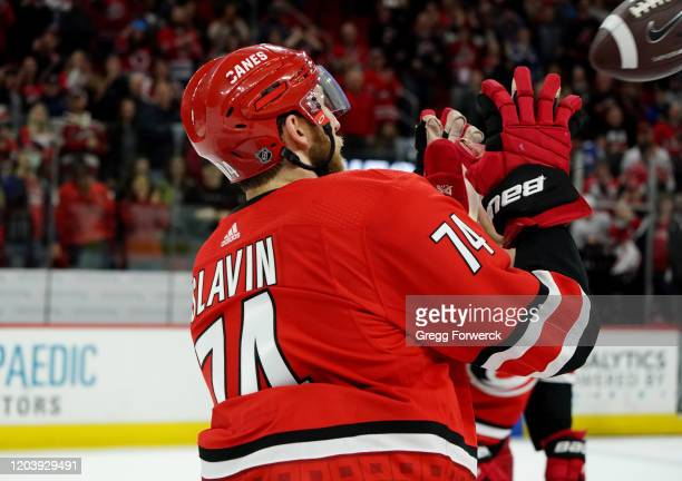 Jaccob Slavin of the Carolina Hurricanes catches a football on super bowl Sunday as he participates in a Storm Surge following an NHL game against...