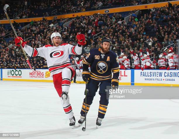 Jaccob Slavin of the Carolina Hurricanes celebrates his game winning overtime goal as Ryan O'Reilly of the Buffalo Sabres reacts during an NHL game...