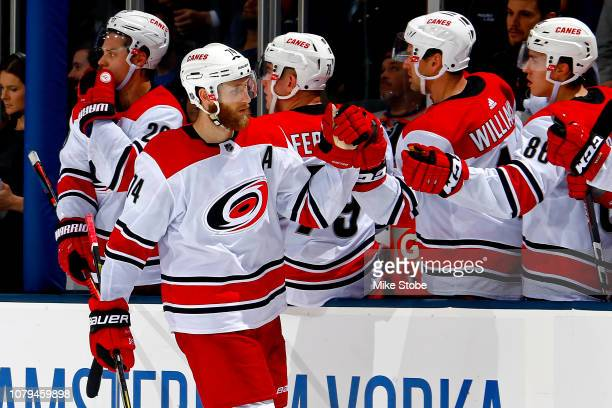 Jaccob Slavin of the Carolina Hurricanes is congratulated by his teammates after scoring a third period goal against the New York Islanders at Nassau...