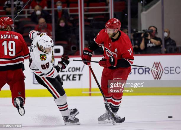 Jaccob Slavin of the Carolina Hurricanes separates Patrick Kane of the Chicago Blackhawks from the puck during an NHL game on May 6, 2021 at PNC...
