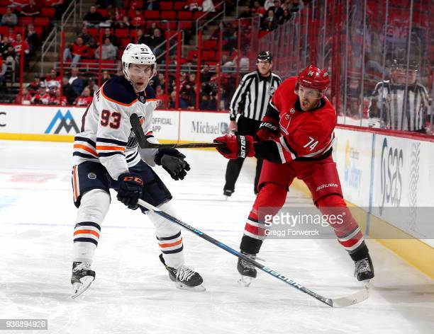 Jaccob Slavin of the Carolina Hurricanes shoots the puck past the defense of Ryan NugentHopkins of the Edmonton Oilers during an NHL game on March 20...