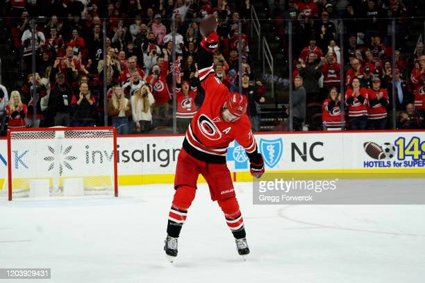Jaccob Slavin of the Carolina Hurricanes spikes a football on Super Bowl Sunday as he participates in a Storm Surge following an NHL game against the...