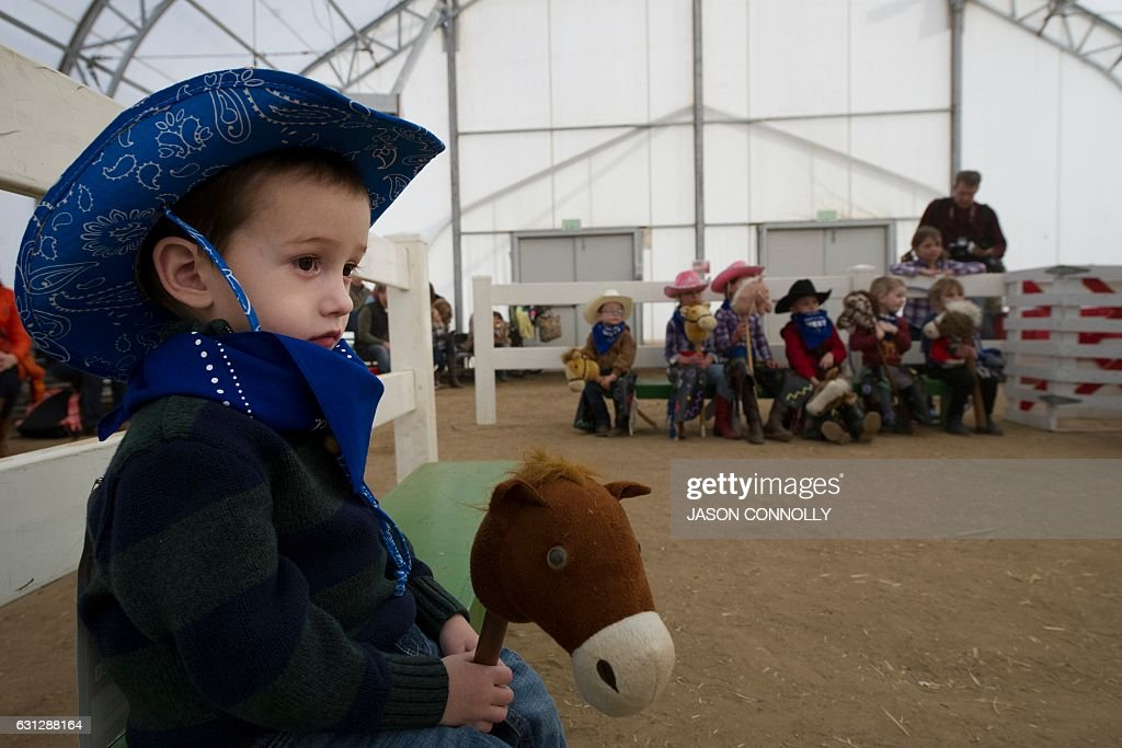 Jace Beck of Lander, Wyoming holds his toy horse while watching other children play during the Stick Horse Rodeo in the Activity Pavilion at the National Western Stock Show in Denver, Colorado on January 8, 2017. Established in 1911, the National Western Stock Show is the premier livestock, rodeo, and horse show in the United States. / AFP / Jason Connolly