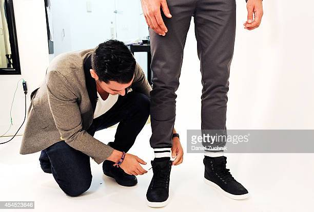 Jace Lipstein CEO and designer of Grungy Gentleman fits a pair of gray pants on model Clayton Straker in the design studio on September 2 2014 in New...