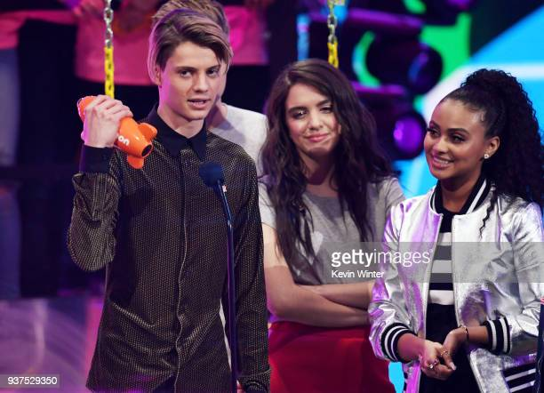 Jace Norman accepts the Favorite TV Actor award for 'Henry Danger' from Lilimar Hernandez and Daniella Perkins onstage at Nickelodeon's 2018 Kids'...