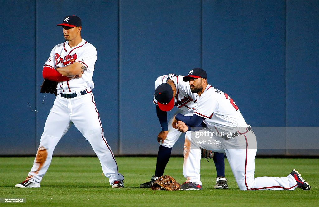 Jace Peterson #8, Mallex Smith #17 and Nick Markakis #22 of the Atlanta Braves look on during a pitching change in the 10th inning against the Los Angeles Dodgers at Turner Field on April 20, 2016 in Atlanta, Georgia.