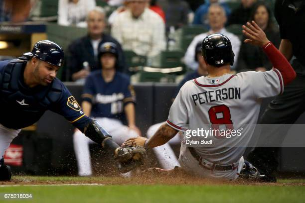 Jace Peterson of the Atlanta Braves slides into home plate to score a run past Manny Pina of the Milwaukee Brewers in the seventh inning at Miller...