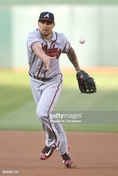 Jace Peterson of the Atlanta Braves underhands the ball to the pitcher covering first base against the Oakland Athletics in the bottom of the first...