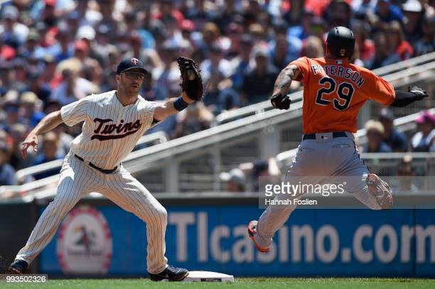 Jace Peterson of the Baltimore Orioles is out at first base as Joe Mauer of the Minnesota Twins fields the ball during the second inning of the game...