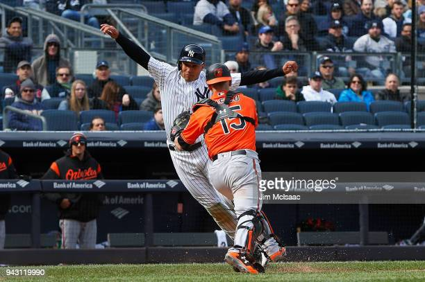 Jace Peterson of the New York Yankees is tagged out during a run down by Chance Sisco of the Baltimore Orioles ending the eighth inning at Yankee...