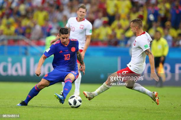 Jacek Goralski of Poland tackles James Rodriguez of Colombia during the 2018 FIFA World Cup Russia group H match between Poland and Colombia at Kazan...