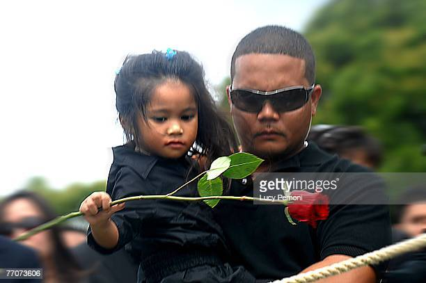 JaceLynn Tolentino niece of Sgt Alexander Udarbe Gagalac of Wahiawa Hawaii throws her rose on her uncle's grave as Joseph Tolentino Gagalac's...