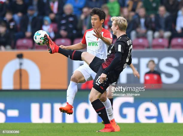 JaCheol Koo of Augsburg and Julian Brandt of Bayer 04 Leverkusen compete for the ball during the Bundesliga match between FC Augsburg and Bayer 04...