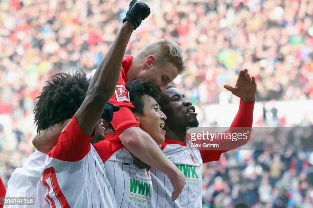Jacheol Koo of Augsburg celebrates his team's first goal with team mates Kevin Danso Martin Hinteregger and Caiuby during the Bundesliga match...