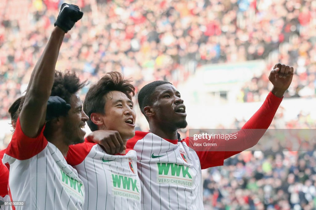 Ja-cheol Koo (2R) of Augsburg celebrates his team's first goal with team mates Kevin Danso (R) and Caiuby during the Bundesliga match between FC Augsburg and Eintracht Frankfurt at WWK-Arena on February 4, 2018 in Augsburg, Germany.