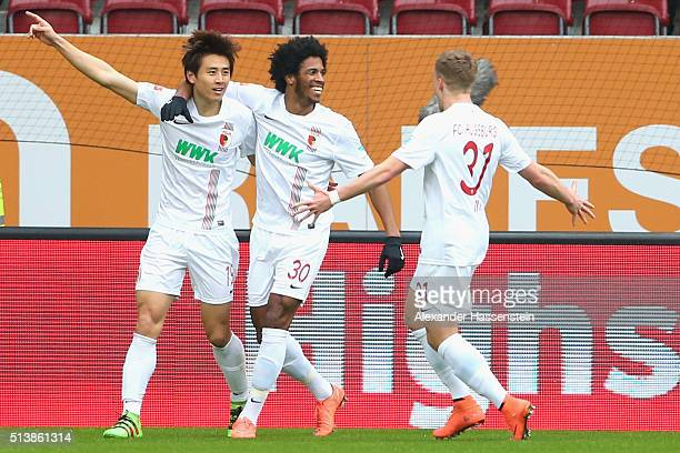 JaCheol Koo of Augsburg celebrates scoing the opening goal with his team mates Caiuby Francisco da Silva and Philipp Max during the Bundesliga match...