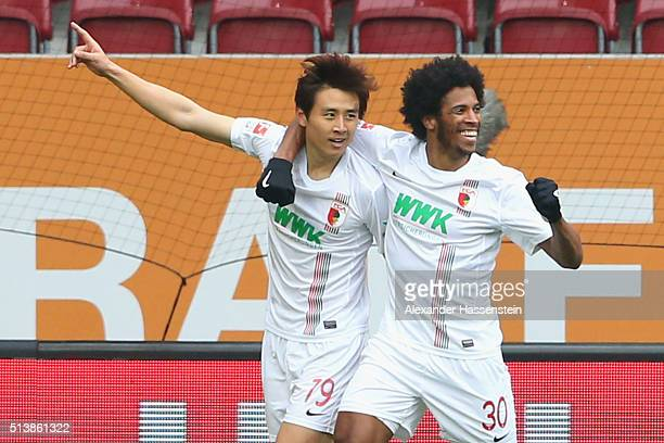 JaCheol Koo of Augsburg celebrates scoing the opening goal with his team mate Caiuby Francisco da Silva during the Bundesliga match between FC...