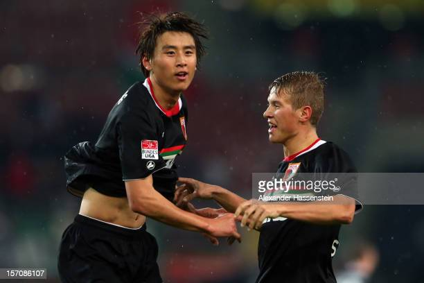 JaCheol Koo of Augsburg celebrates scoring his first team goal with his team mate Matthias Ostrzolek during the Bundesliga match between VfB...